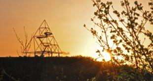 Die Stahlkonstruktion einer dreiseitigen Pyramide vor untergehener Sonne