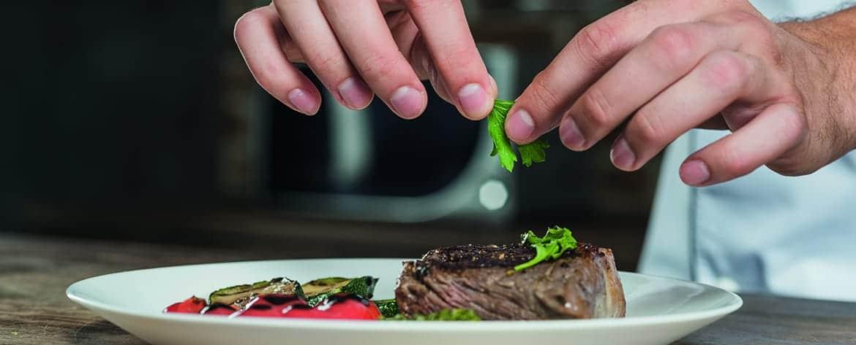 Koch garniert Teller - Restaurantmarketing mit hoga-presse